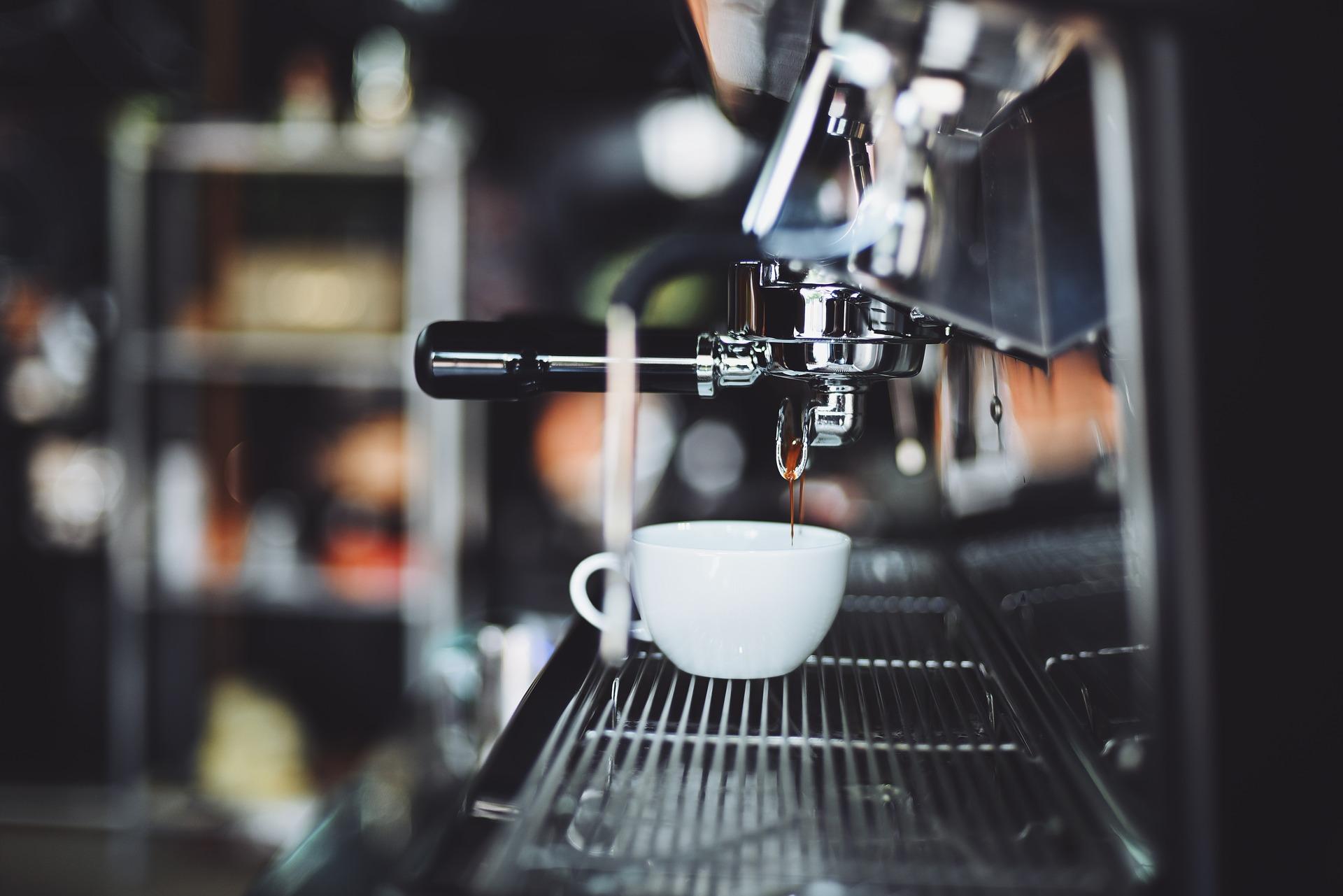 Auf einer Kaffeemaschine steht eine weiße Tasse.